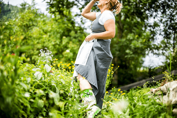 Biobäuerin steht im Hausgarten und blickt in den Himmel.