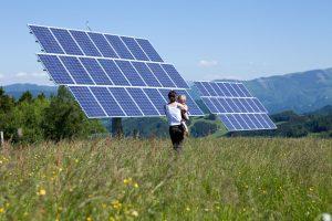 Mutter mit Kind im Arm vor Solaranlage