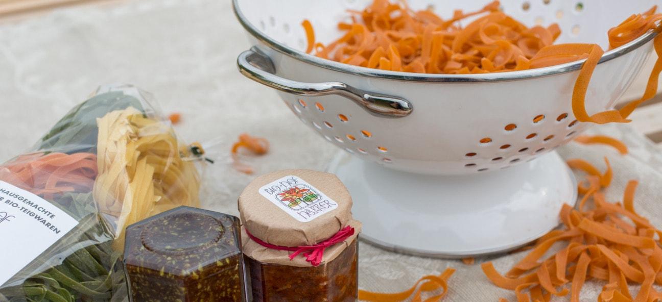 Bio-Nudeln und Bio-Pesto schön drapiert am Tisch, Produktfotografie