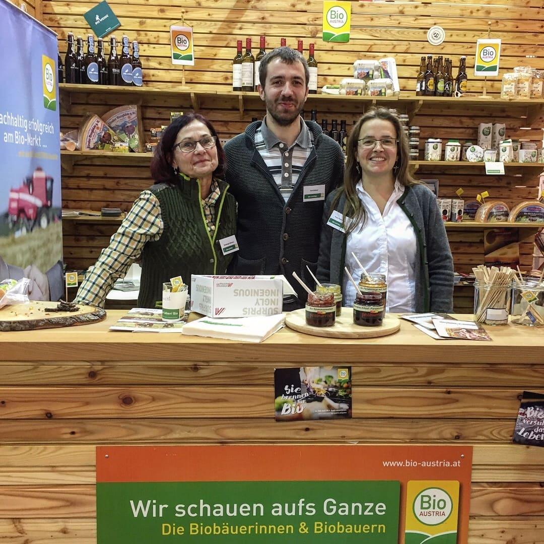 Infostand von BIO AUSTRIA auf der Weltleitmesse für Bio der BIOFACH 2018, drei Mitarbeiter stehen vor dem Infostand und informieren Personen.