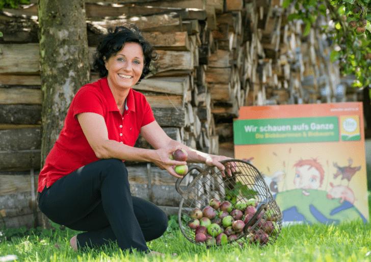 GF Susanne Maier mit Bio-Pressobst im Korb auf einer Wiese.