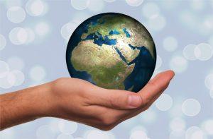 Weltkugel wird in Hand gehalten